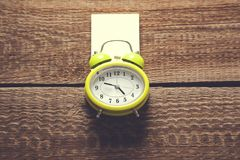 Paper and alarm clock on brown wooden background royalty free stock image
