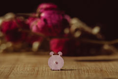 Paper alarm-clock. Macro photo of pink paper alarm-clock in front of red flowers Royalty Free Stock Images
