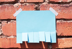 Paper for announcement. On a brick wall with shadows from sunlight Royalty Free Stock Photo