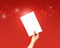 Paper on arm and hand holding on red bokeh background. With copy space Royalty Free Stock Images