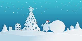 Paper art concept of christmas with Santa Claus carries a bag of gifts in snow scene to village.Merry christmas and happy new year Royalty Free Stock Images