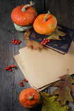 Paper with autumn leaves, pumpkin and book on wooden background Royalty Free Stock Photo