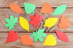 Paper autumn leaves shaped and trimmed with scissors. Simple form of homemade decor. Many colored paper leaves design Stock Photos