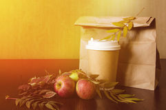 Paper bag, autumn leaves and hot cup of coffee. Business lunch concept. Paper bag, autumn leaves and hot steaming cup of coffee. Business lunch concept Royalty Free Stock Photography