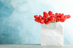 Paper bag with beautiful red tulips on table against blue background stock photography