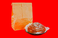 Paper bag with  bun  on a red background Stock Images