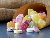 Paper bag of candy sweets. Sugar candy in paper bag placed on blue table Royalty Free Stock Image
