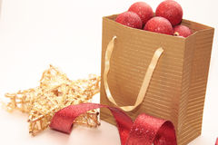 Paper bag with Christmas ornaments. Ribbon and gold star Royalty Free Stock Photography