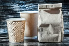 Paper bag and cups on vintage wood stock image