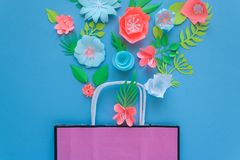 Paper bag of different paper flower on a blue background. Shopping. Top view. Flat lay Royalty Free Stock Images