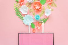 Paper bag of different paper flower on a pink background. Shopping. Top view. Flat lay Stock Images