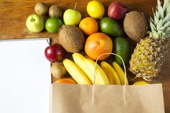 Paper bag of different fruits with notepad on wooden background. Flat lay. Top view. Copy space royalty free stock photography