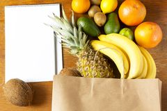 Paper bag of different fruits with notepad on wooden background. Flat lay. Top view. Copy space stock images