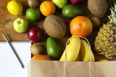 Paper bag of different fruits with notepad on wooden background. Flat lay. Top view stock images