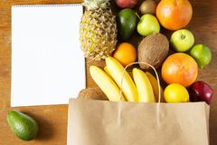 Paper bag of different fruits with notepad on wooden background. Flat lay. Top view. Copy space stock photos