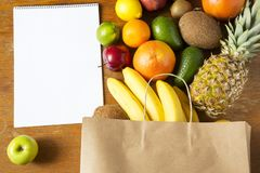 Paper bag of different fruits with notepad on wooden background. Flat lay. Top view. Copy space royalty free stock photos