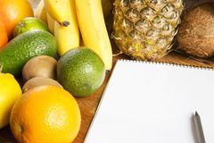 Paper bag of different fruits with notepad on wooden background. Side view. Closeup. Copy space stock images