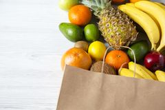 Paper bag of different fruits on white wooden background. Flat lay. Top view. Copy space royalty free stock photo