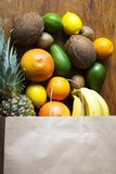 Paper bag of different fruits on wooden background. Flat lay. Top view Royalty Free Stock Photo