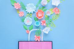Paper bag of different paper flower on a blue background. Shopping. Top view. Flat lay Royalty Free Stock Photos