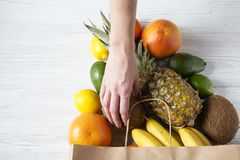 Paper bag of different tropical fruits on white wooden background. Female hand holding coconut. Flat lay. Top view royalty free stock photos