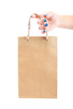 Paper bag in a female hand on white background. Stock Image