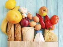 Paper bag food ingredient product various milk garlic cheese onion mandarin blue wooden stock image