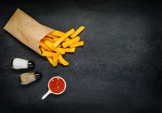 Paper Bag with French Fries and Condiments on Copy Space Royalty Free Stock Photos
