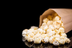 Paper bag with fresh popcorn, black background Royalty Free Stock Photography