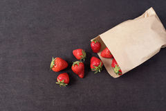 Paper bag with fresh red strawberries. Fresh strawberries in a small bag on a wooden style surface. Small group of strawberries on Stock Photo