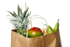 Paper bag with fresh tropical fruits. On white background Stock Image