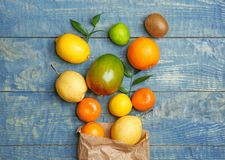 Paper bag and fresh tropical fruits. On wooden background Stock Photography