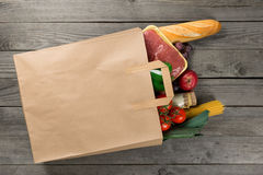 Paper bag full of different food on wooden background. Close up. Grocery shopping concept, top view Royalty Free Stock Images