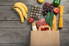 Paper bag full of different food on wooden table Stock Photo