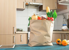 Paper bag full of healthy food on blue wooden table Royalty Free Stock Image