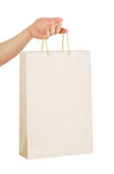 Paper bag in hand. Human hand carry blank slate beige paper bag isolated on white background Stock Photography