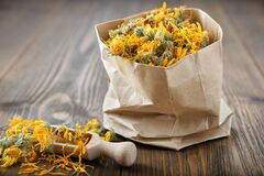 Paper bag of healing calendula herbs and wooden scoop of dry marigold flowers.