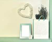 Paper bag with lavender flowers, picture frame with empty blank, heart shape over white wall royalty free stock image