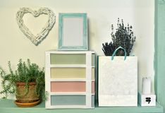 Paper bag with lavender, succulent plant and picture frame on wooden shelf royalty free stock photography