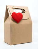 Paper bag with red heart over wrapping paper on white background Stock Images