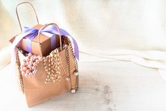 Paper bag for shopping fashion accessories. Light pink scarf , a bracelet lying on the wooden background Royalty Free Stock Image