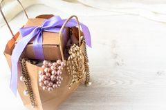 Paper bag for shopping fashion accessories. Light pink scarf , a bracelet lying on the wooden background Royalty Free Stock Photo