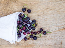 Paper bag of sweet cherries ona rough wood background Stock Photos