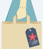Paper bag tagged with a starfish, symbol of summer Royalty Free Stock Photos