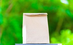 paper bag on the wood and tree blurry bokeh background in garden. Using wallpaper for package work photo. Stock Photos