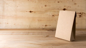 Paper bag on wooden background Stock Images
