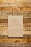 Paper bag on a wooden texture Royalty Free Stock Photography