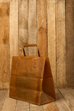 Paper bag on a wooden texture Stock Photos