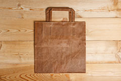 Paper bag on a wooden texture Royalty Free Stock Images