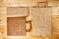 Paper bag on a wooden texture Royalty Free Stock Photos